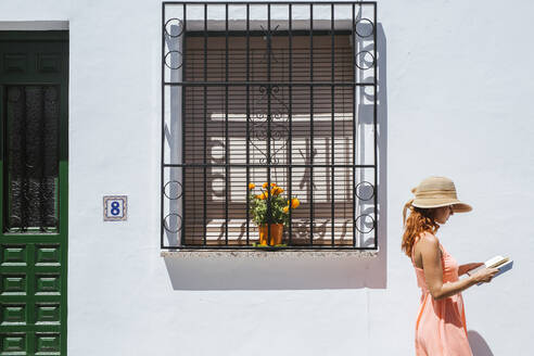 Redheaded young woman reading a book in front of a house, Frigiliana, Malaga, Spain - LJF00681