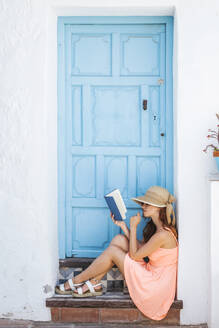 Young woman sitting on step of house entrance reading a book, Frigiliana, Malaga, Spain - LJF00690