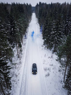 Aerial view of a man lighting a blue smoke grenade on a snowy road in the forest in Estonia - AAEF02488