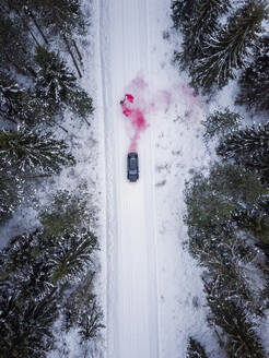 Aerial view of a man lighting a pink smoke grenade on a snowy road in the forest in Estonia - AAEF02491