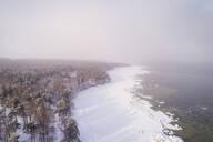 Aerial view of the snowy misty coast of Muraste in Estonia - AAEF02494
