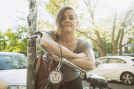 Portrait of tattooed woman with a bike in the city - TAMF02053