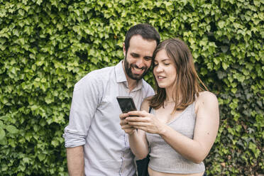 Happy young couple sharing cell phone - TAMF02095