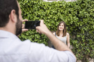 Man taking cell phone picture of young woman at a hedge - TAMF02098