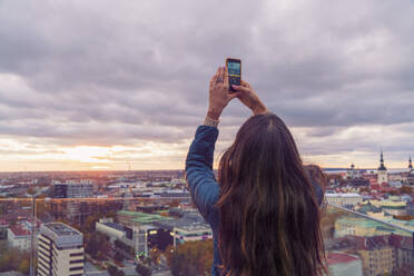 Woman taking a photo with smartphone from a view terrace before sunset, Tallinn, Estonia - TAMF02137