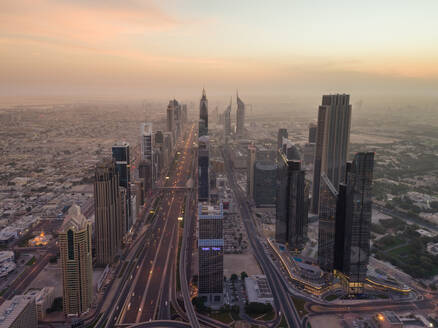 Aerial view of the traffic lanes and Skyscrapers in Dubai at sunset, U.A.E. - AAEF02715