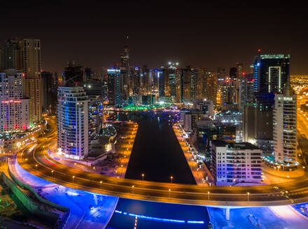 Aerial view of illuminated skyscrapers and canal in Dubai at night, U.A.E. - AAEF02790