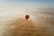 Aerial view of a group of hot-air-balloon flying in the clouds of the Murqquab desert in Dubai, UAE - AAEF02889