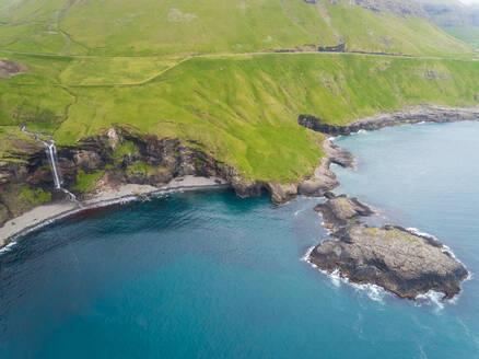 Aerial view of small waterfall ending on North Atlantic sea, Faroe island - AAEF02961