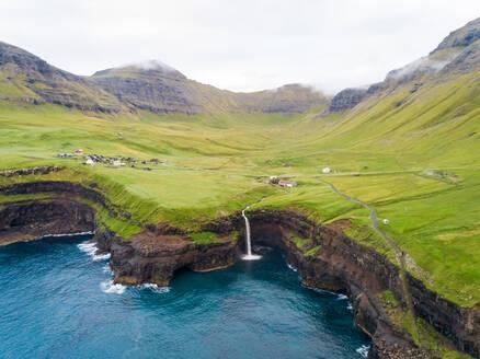 Aerial view faraway of Múlafossur waterfall near a small village, Faroe island. - AAEF02982