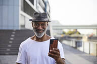 Portrait of happy mature man with cell phone - FMKF05887