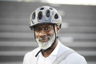 Portrait of smiling mature businessman with grey beard wearing cycling helmet and glasses - FMKF05896