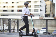 Mature businessman riding E-Scooter - FMKF05899