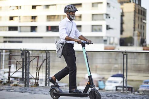 Mature businessman riding E-Scooter - FMKF05899