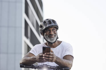 Portrait of happy mature man wearing cycling helmet leaning on handlebar of Electric Scooter - FMKF05902