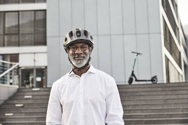 Portrait of smiling mature businessman with E-Scooter wearing cycling helmet - FMKF05905
