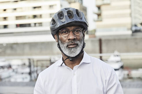 Portrait of mature businessman with grey beard wearing cycling helmet and glasses - FMKF05908