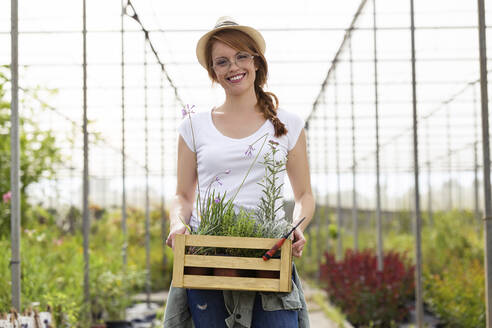 Portrait of beautiful young woman holding wooden box with plants in the greenhouse - JSRF00513