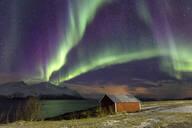 Northern Lights illuminates the wooden cabin at Svensby, Lyngen Alps, Troms, Lapland, Norway, Scandinavia, Europe - RHPLF00989