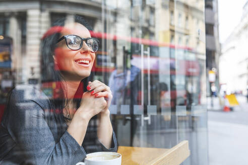 Smiling woman behind windowpane in a cafe - WPEF01802