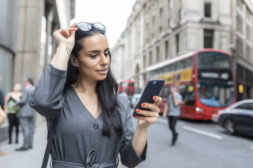 Business woman near a busy street checking her smartphone, London, UK - WPEF01805