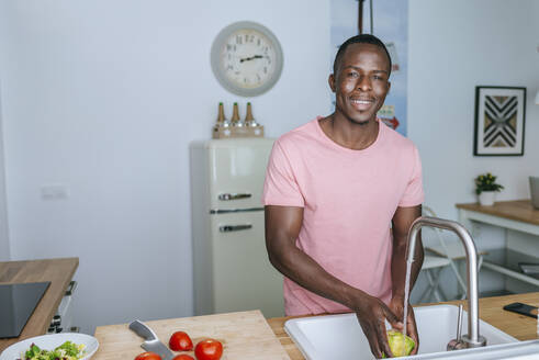 Portrait of smiling young man washing lettuce in kitchen - KIJF02600