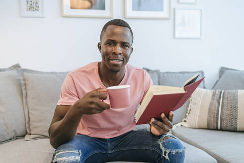 Portrait of young man with book and cup of coffee at home - KIJF02609