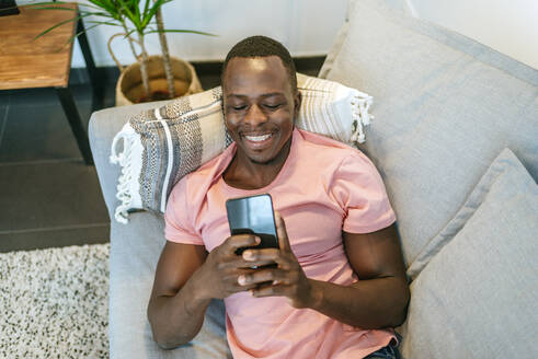 Happy young man lying on the couch with smartphone at home - KIJF02612