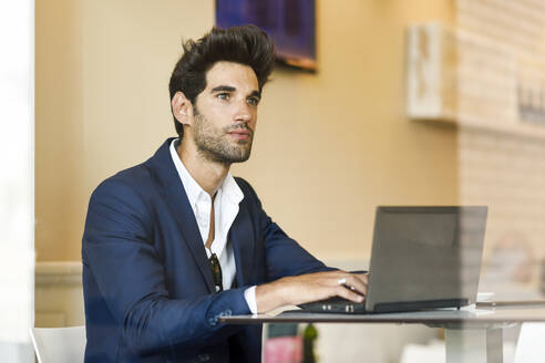 Businessman using laptop in an urban cafe - JSMF01213