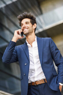 Happy businessman talking on cell phone outside an office building - JSMF01222
