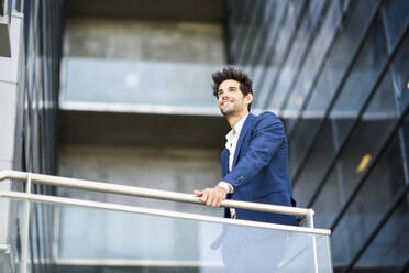 Smiling businessman standing on balcony of an office building - JSMF01228