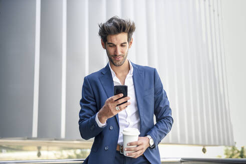 Smiling businessman using smartphone taking a coffee break outdoors - JSMF01234