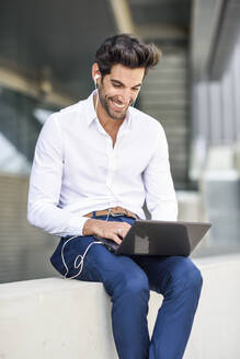 Smiling businessman wearing earphones using laptop outdoors in the city - JSMF01237