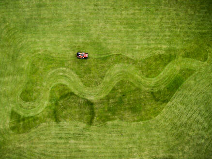 Aerial photography of man on lawnmower creating shapes in grass - AAEF03588