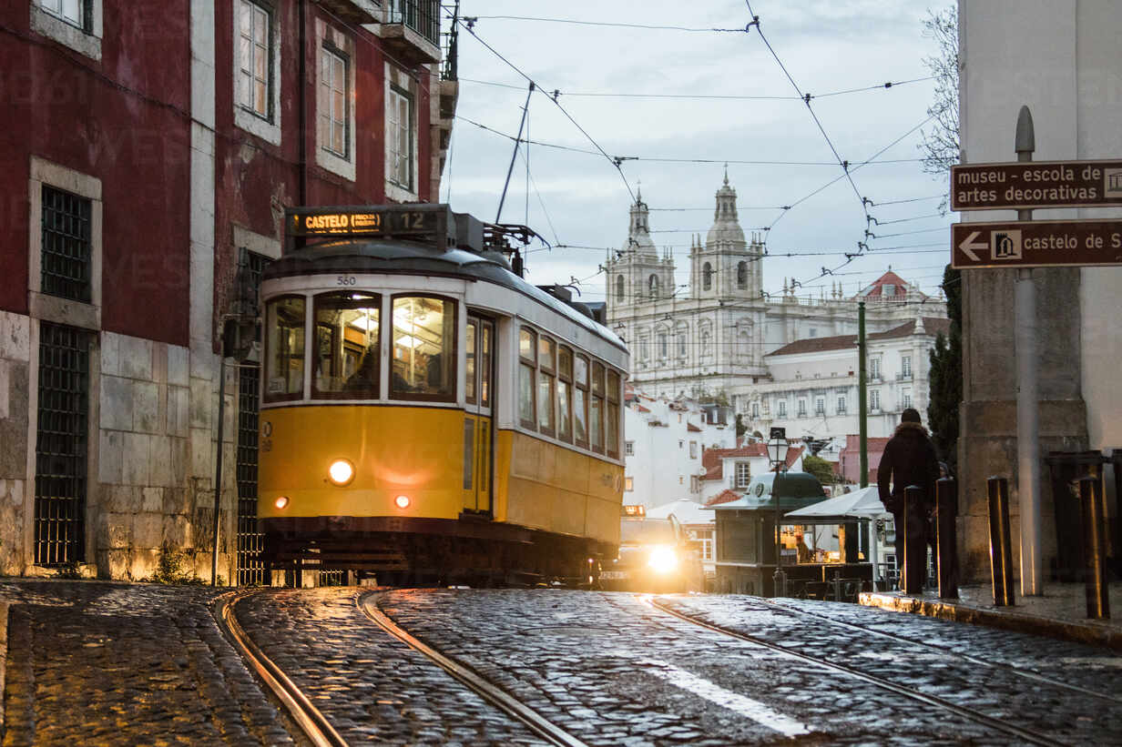 Romantic Atmosphere In The Old Streets Of Alfama With The Castle In The Background And Tram