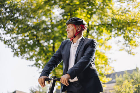 Portrait of smiling senior man with e-scooter in the city - GUSF02379
