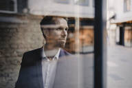 Portrait of businessman looking out of window - GUSF02388