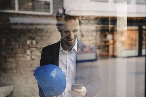Smiling businessman with hard hat looking at cell phone - GUSF02391