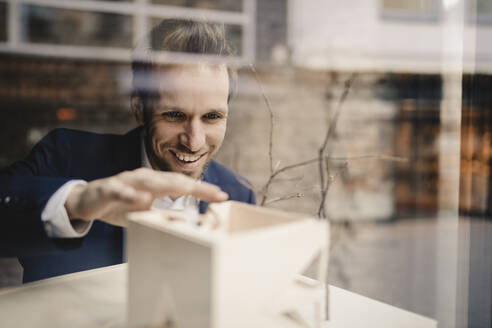 Smiling businessman with architectural model - GUSF02394