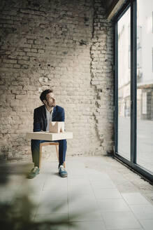 Businessman sitting at brick wall with architectural model - GUSF02403