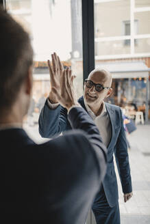 Senior and mid-adult businessman high fiving - GUSF02406