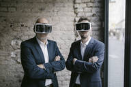 Senior and mid-adult businessman wearing VR glasses - GUSF02421