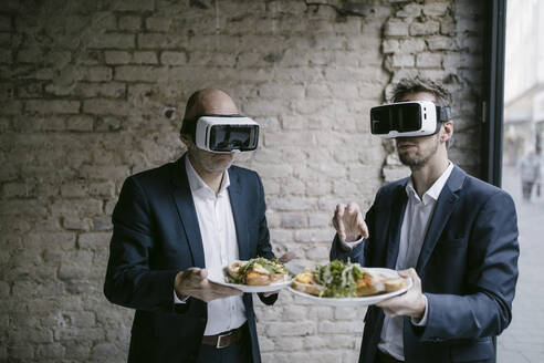 Senior and mid-adult businessman wearing VR glasses holding plate with a meal - GUSF02424