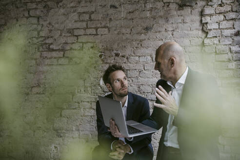 Senior and mid-adult businessman having a meeting using laptop - GUSF02430