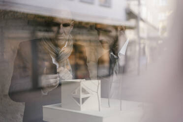 Senior and mid-adult businessman with architectural model behind windowpane - GUSF02436