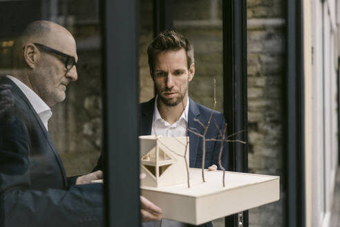 Senior and mid-adult businessman with architectural model - GUSF02442