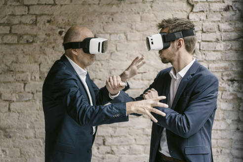 Senior and mid-adult businessman wearing VR glasses fighting - GUSF02445