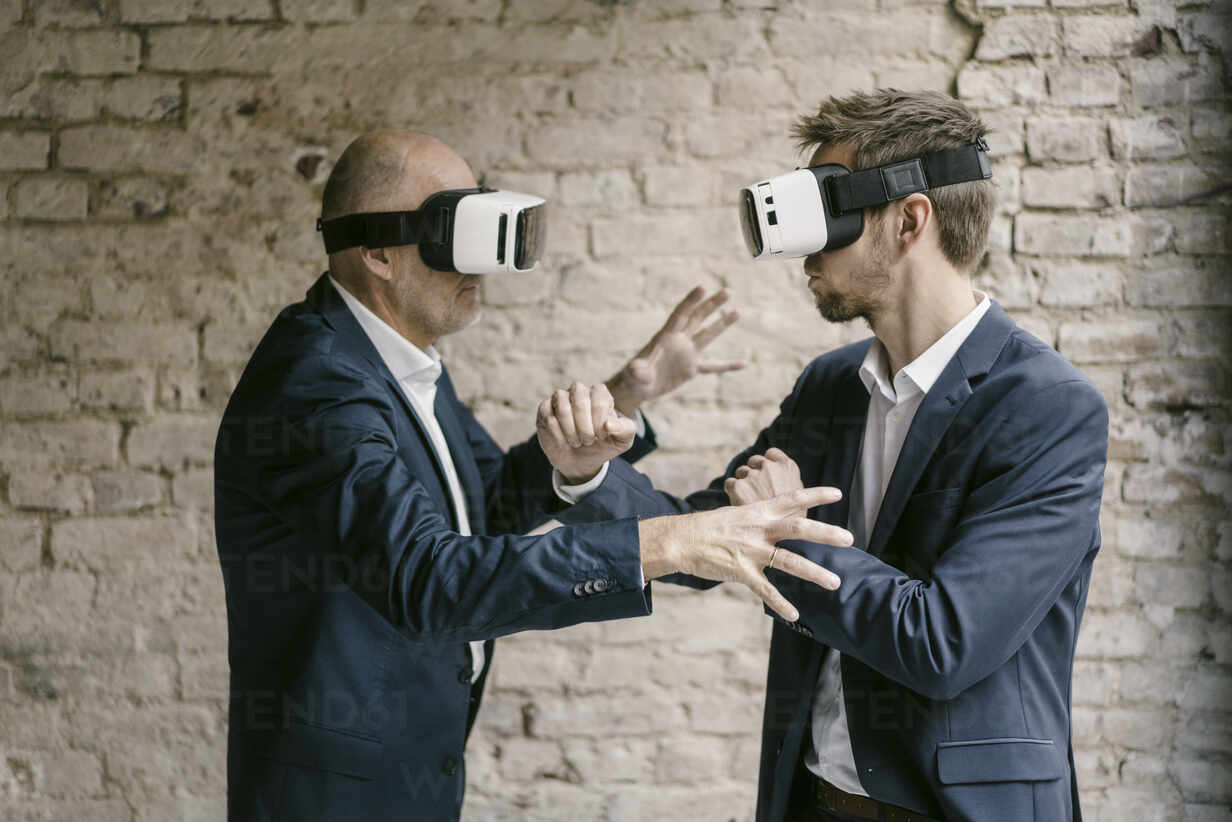Senior and mid-adult businessman wearing VR glasses fighting - GUSF02445 - Gustafsson/Westend61