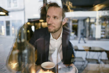 Portrait of businessman in a cafe looking out of window - GUSF02448