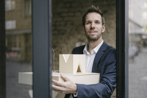 Portrait of businessman holding architectural model - GUSF02451